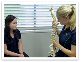 Photo of a Physiotherapist showing a patient a skeletal spine and hip model